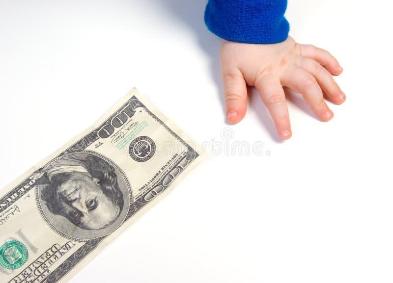 De hand van kinderen en de dollar stock fotografie