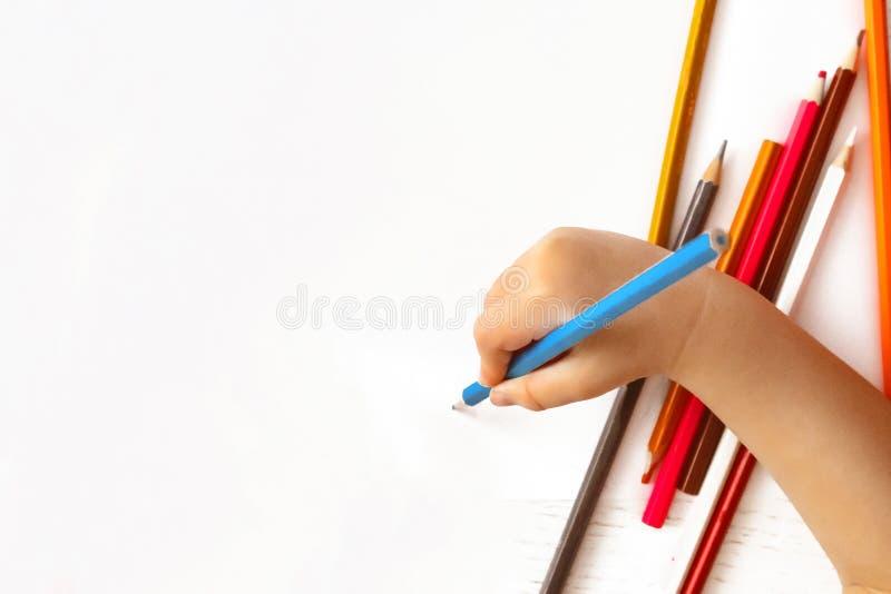 De hand van kinderen trekt een potlood op Witboek stock afbeeldingen