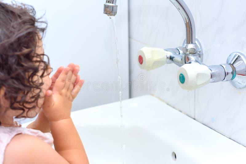 De hand van de kindwas met water Om het griepvirus bij baai te houden, was uw handen met zeep en geef meerdere keren per dag wate stock afbeelding