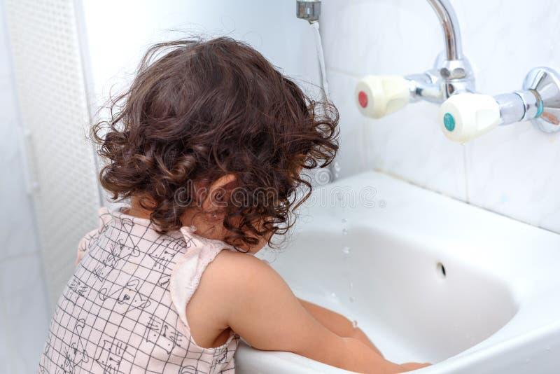 De hand van de kindwas met water Om het griepvirus bij baai te houden, was uw handen met zeep en geef meerdere keren per dag wate stock fotografie