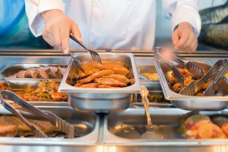 De hand van kok neemt tangen gebraden vlees royalty-vrije stock afbeelding