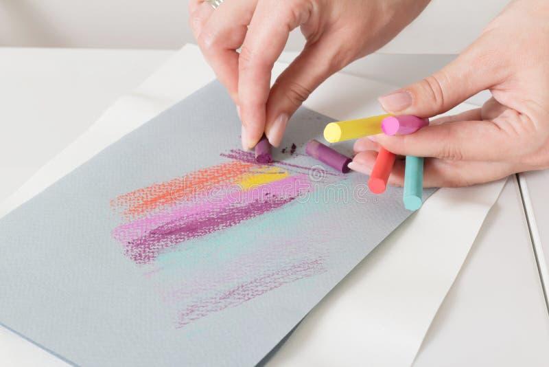 De hand van de kunstenaar trekt krijtpastelkleuren op document abstracte lijnen royalty-vrije stock afbeeldingen
