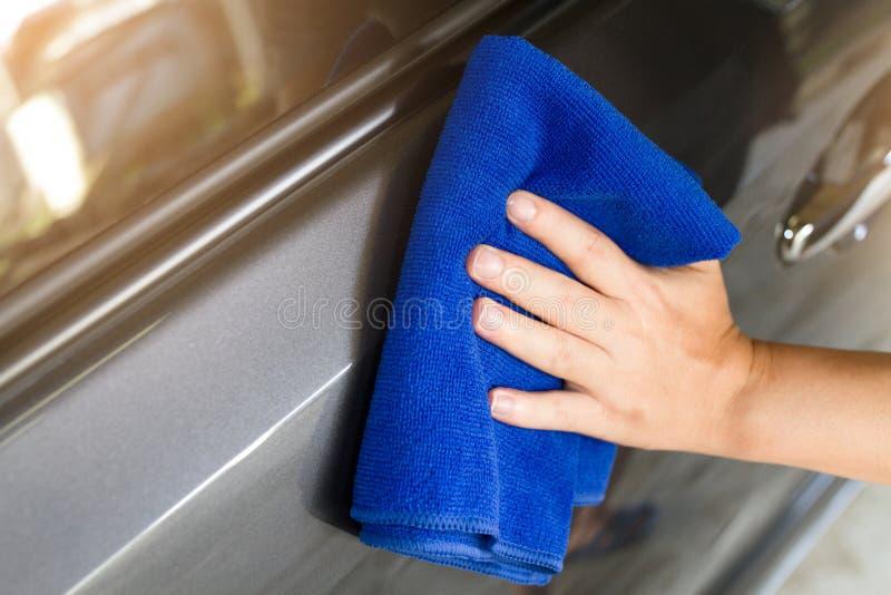 De hand van de man gebruikt blauwe microfiber stock fotografie