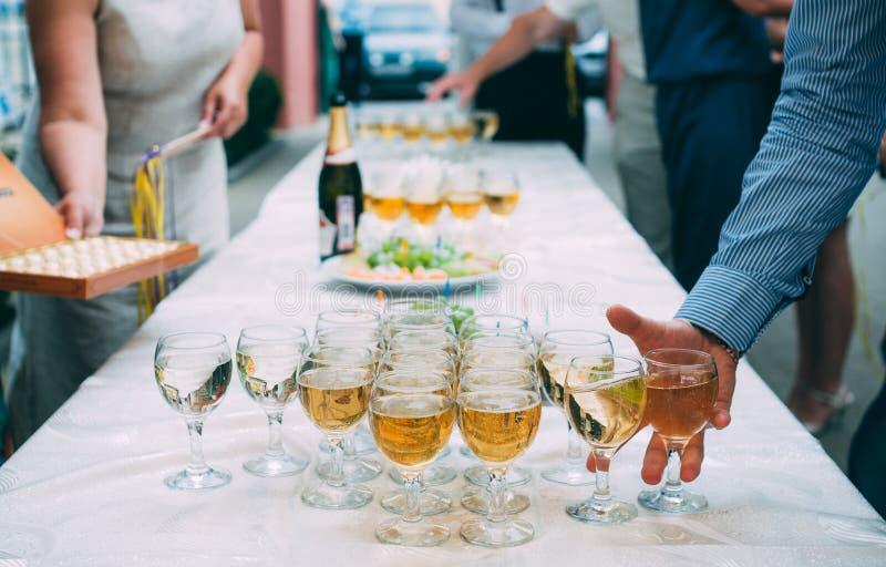 De hand van mensen neemt een glas champagne bij stock fotografie