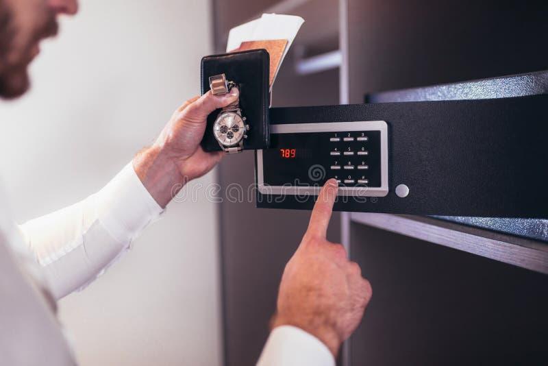 De hand van mensen opent een brandkast die in de garderobe wordt verborgen stock fotografie