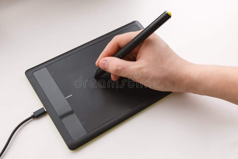De hand van mensen trekt op een grafiektablet gebruikend een naald stock afbeeldingen