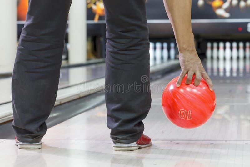De hand van mensen werpt kegelenbal op de close-ups van kegelenspelden stock foto