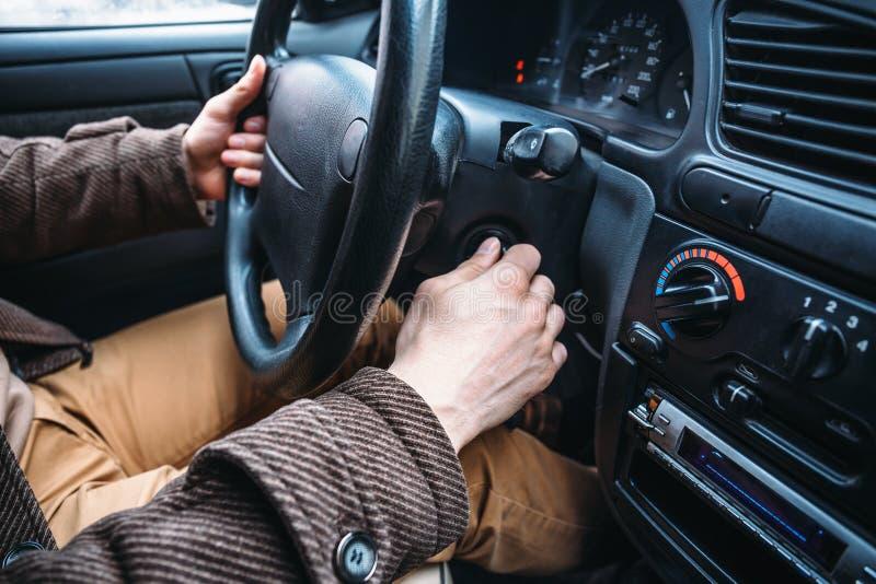 De hand van de mensenbestuurder zet autosleutel aan sleutelgat om zijn auto te beginnen royalty-vrije stock afbeelding