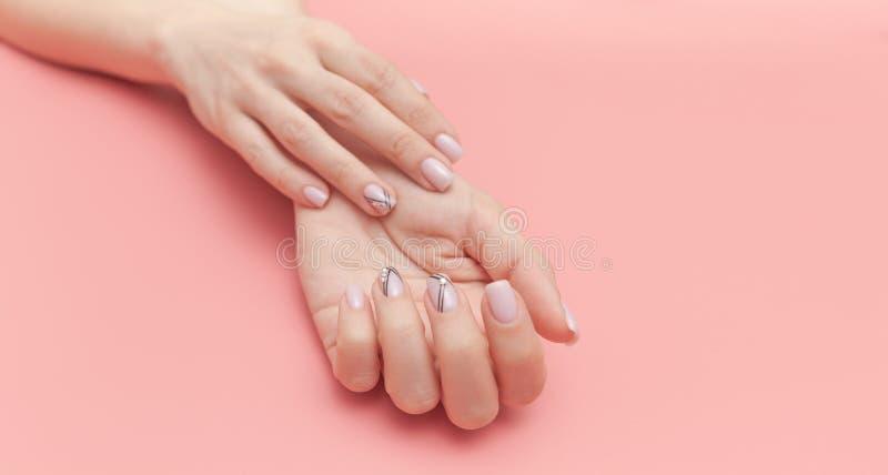 De hand van de mooie jonge vrouw met perfecte manicure op roze achtergrond vlak leg stijl stock afbeeldingen