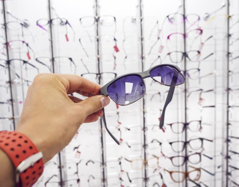 De hand van de persoon kiezen glazenzonnebril bij de opticaopslag stock foto's