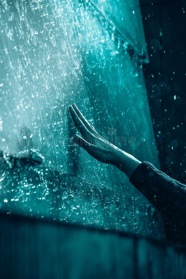 De hand van de persoon wat betreft een waterige muur met water druipt en een donkere achtergrond royalty-vrije stock afbeeldingen