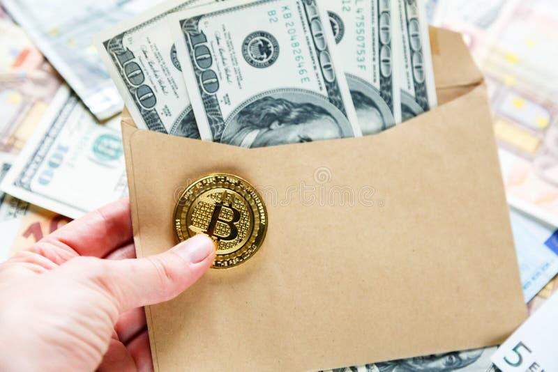 De hand van de vrouw houdt een envelop met dollars en bitcoin Investering, risico, salaris, besparingen royalty-vrije stock fotografie