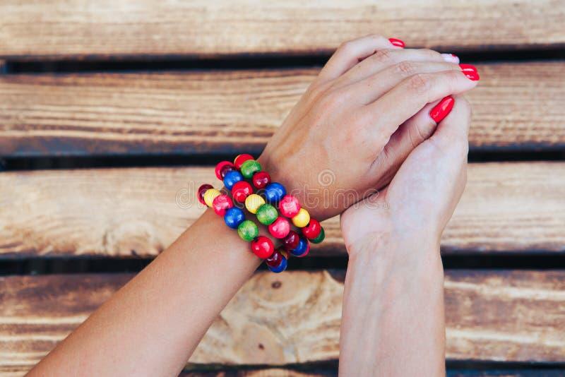 De hand van de vrouw met armband en parels Houten achtergrond Hoogste mening stock fotografie