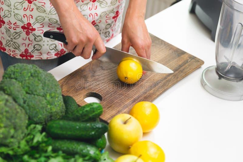 De hand van de vrouw met een messen scherpe citroen op houten raad Groene Smoothie-voorbereiding stock afbeelding