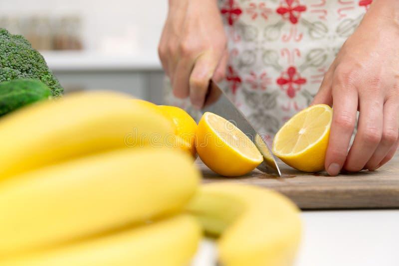 De hand van de vrouw met een messen scherpe citroen op houten raad Groene Smoothie-voorbereiding stock foto