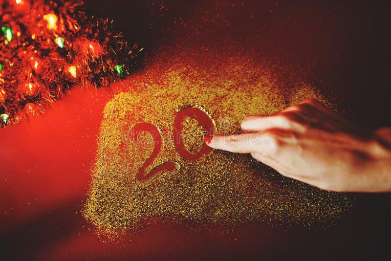 De hand van de vrouw schildert het cijfer van 2020 op de Bordeauxachtergrond met fonkelingen Nieuw jaar`s concept stock afbeeldingen