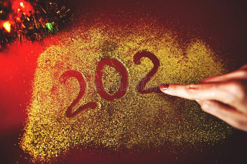 De hand van de vrouw schildert het cijfer van 2020 op de Bordeauxachtergrond met fonkelingen Nieuw jaar`s concept royalty-vrije stock afbeelding