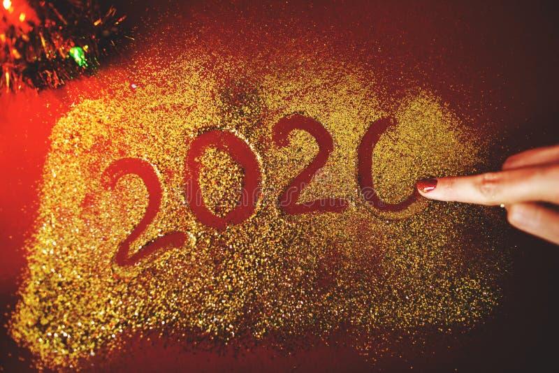 De hand van de vrouw schildert het cijfer van 2020 op de Bordeauxachtergrond met fonkelingen Nieuw jaar`s concept royalty-vrije stock afbeeldingen
