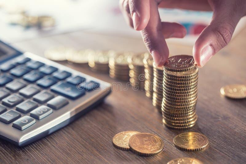 De hand van de vrouw zette euro muntstukken met een de groeieffect Stilleven met cackulator van het businessplan en euro munt royalty-vrije stock foto
