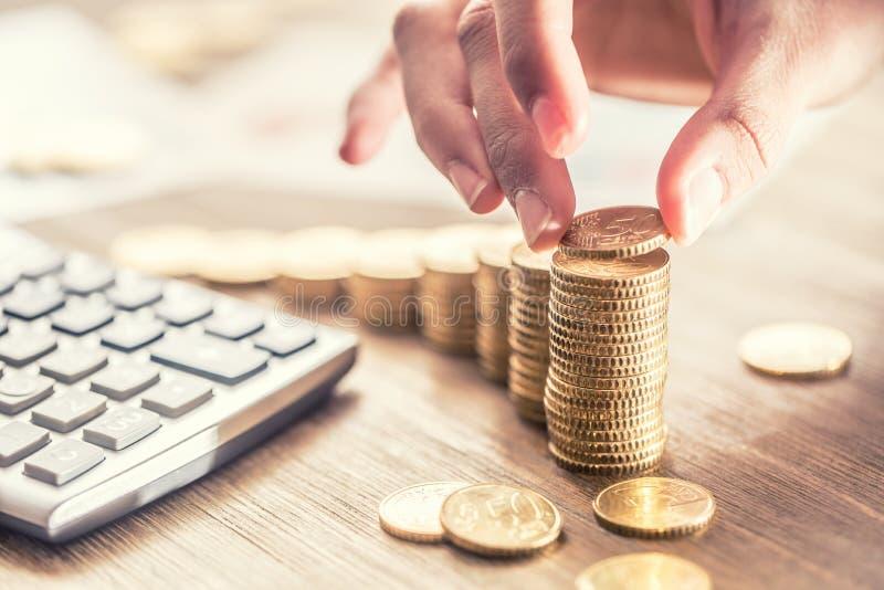 De hand van de vrouw zette euro muntstukken met een de groeieffect Stilleven met cackulator van het businessplan en euro munt stock foto