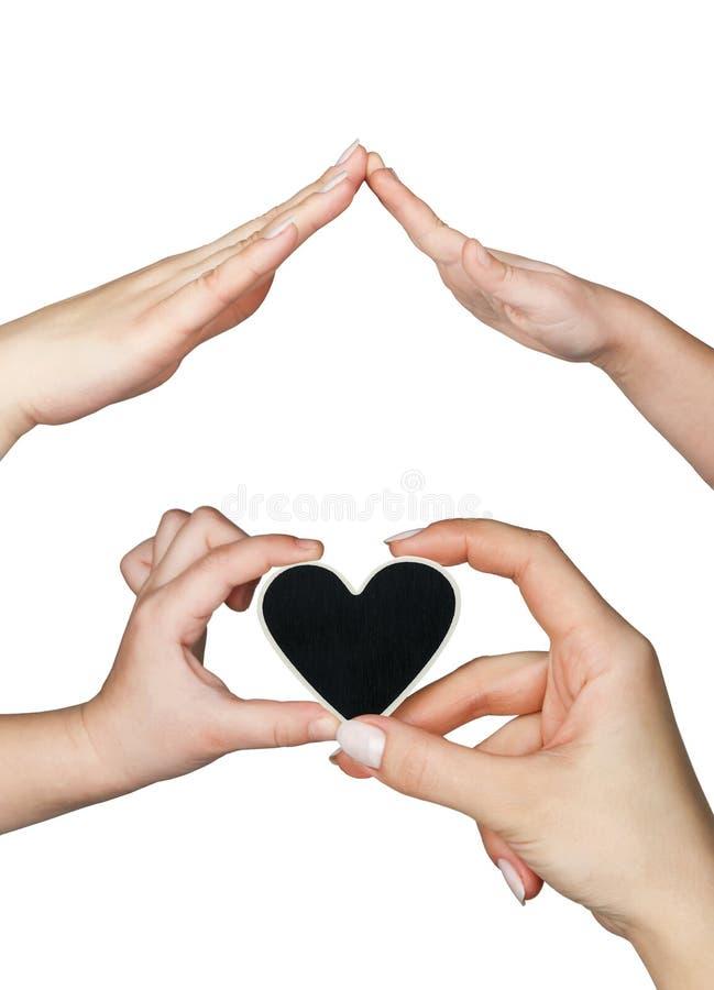 De hand van vrouwen en van kinderen houdt een hart stock foto