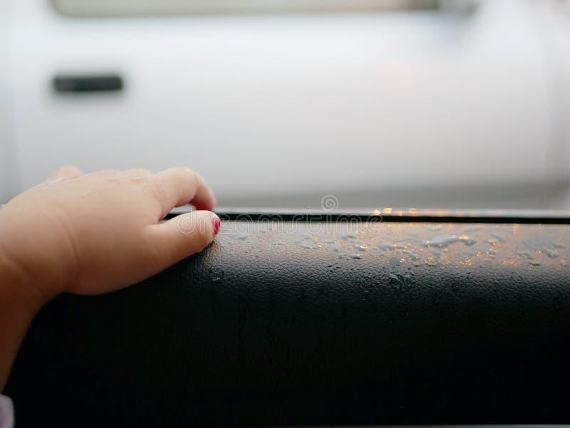 De hand van weinig die baby op het geopende venster van een auto wordt geplaatst om de regen te laten die vallen op stock fotografie