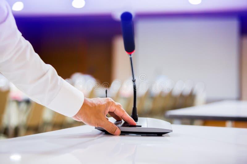 De hand van zakenman is drukkend aan macht op draadloze Conferentiemicrofoons in een vergaderzaal royalty-vrije stock afbeeldingen