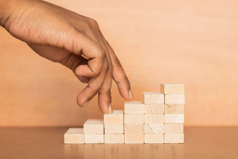 De hand vergelijkt bedrijfspersoon die een houten stuk speelgoed trap op houten geweven achtergrond opvoeren stock afbeeldingen