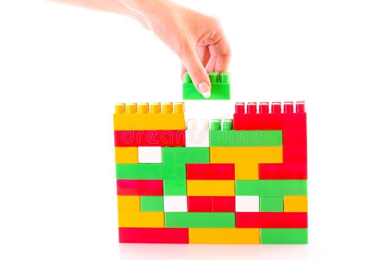 De hand voegt stuk speelgoed baksteen aan stuk speelgoed geïsoleerde de bouw toe stock foto