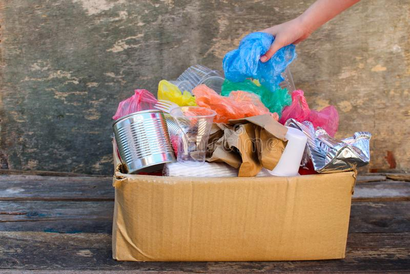De hand werpt huisvuil in een kartondoos stock afbeeldingen