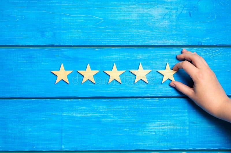 De hand zet de vijfde ster De criticus bepaalt de classificatie van het restaurant, hotel, instelling Kwaliteitsteken overzicht v stock foto's