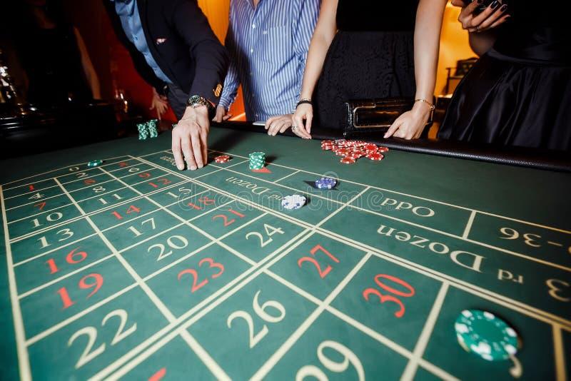De hand zette een weddenschap op de roulette stock afbeelding