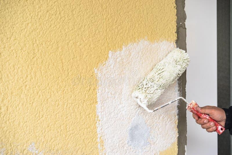 De handarbeider schildert muur met schildersrol royalty-vrije stock fotografie