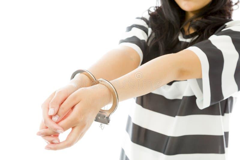 De handboeien om:doen Aziatische jonge vrouw in eenvormige gevangenen stock fotografie
