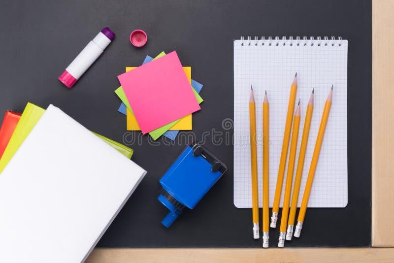 De handboeken en de onderwerpen voor een tekeningsles in school zijn op de achtergrond van een zwart schoolbord stock afbeelding