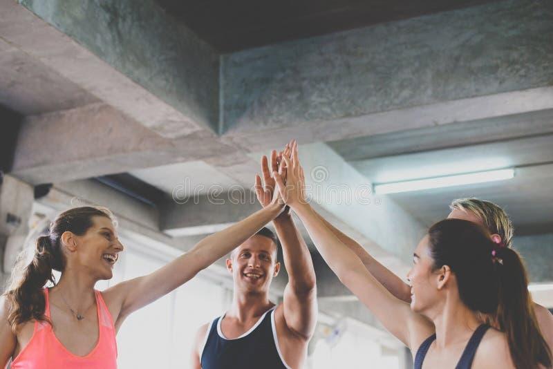 De handcoördinatie van met gemotiveerd, Sportief jong vriendschappelijk aantrekkelijk team glimlachen en groepsmensen die of heft stock afbeeldingen
