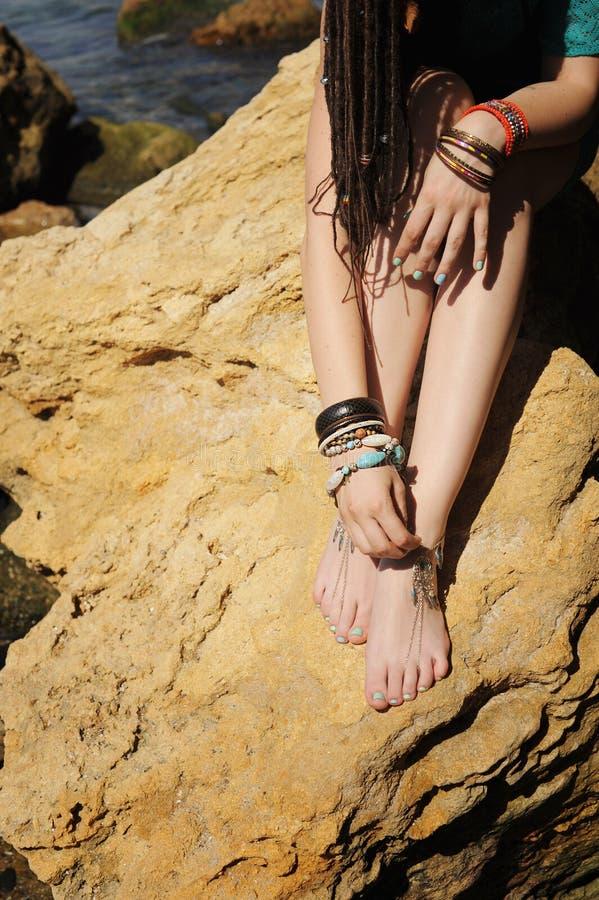 De Handcraftedarmbanden op een vrouwenbenen, sluiten omhoog, witte pedicure stock foto's