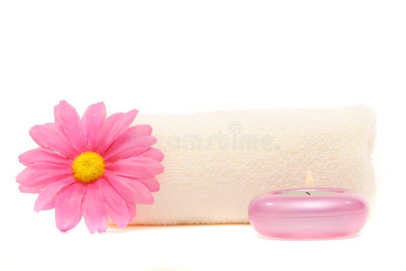 De handdoek van het kuuroord, gerberamadeliefje en kaars stock afbeelding