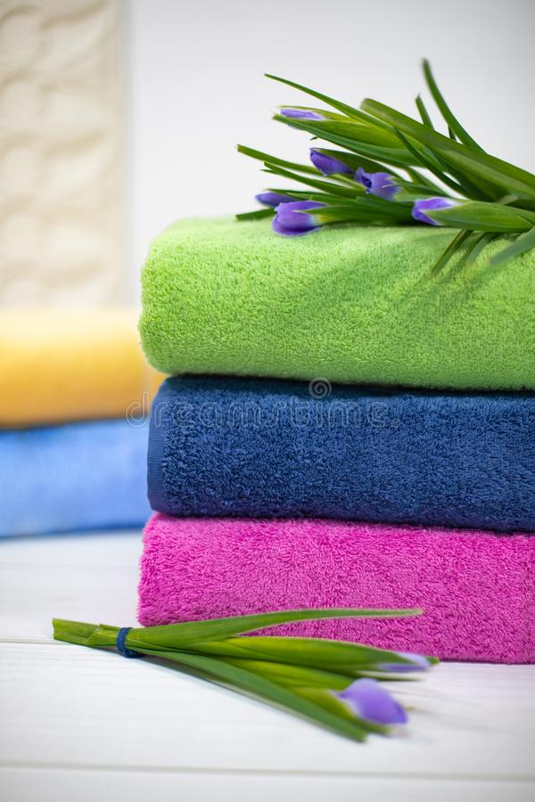 De handdoeken in stapel tegen blured achtergrond Stapel groene, blauwe, yelloy en roze handdoeken met bloemen royalty-vrije stock foto