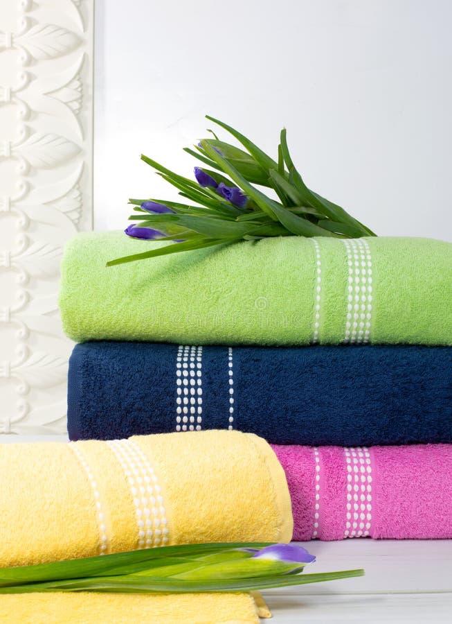 De handdoeken in stapel tegen blured achtergrond, stapel groene, blauwe, yelloy en roze handdoeken met bloemen stock afbeelding