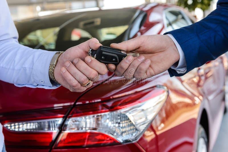 De handelaar die sleutels van nieuwe auto aan klantensluiting geeft royalty-vrije stock foto's