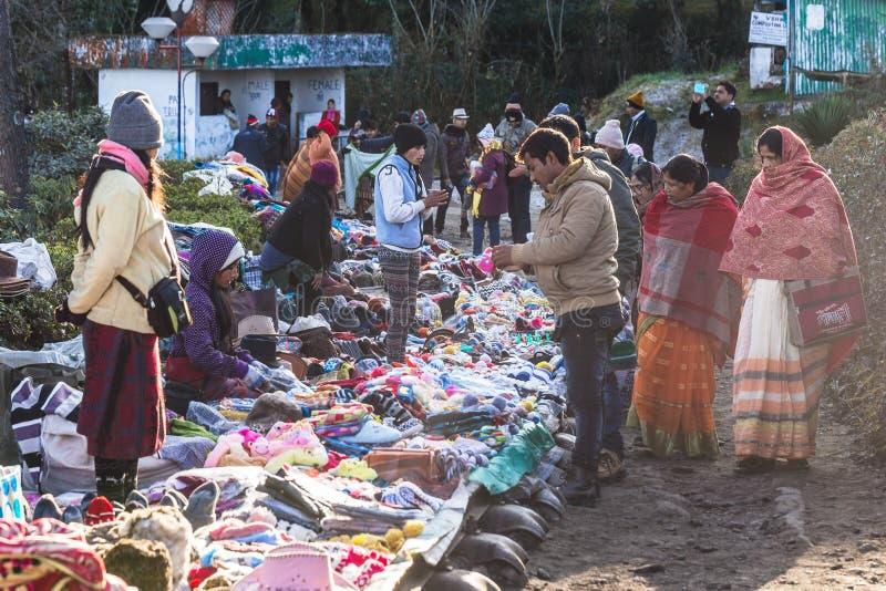 De handelaars en de klanten met laag en kap verkopen kleren op de spoorweg in de winter van Tiger Hill in Darjeeling, India stock foto