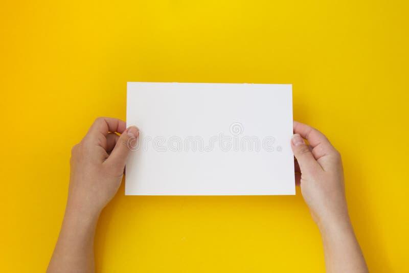 De handen die leeg wit, leeg document houden isoleerden op geel met exemplaarruimte stock foto