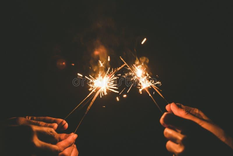 De handen die sterretjes houden voor vieren in de nacht stock afbeelding