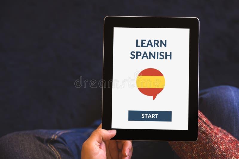De handen die tablet houden met online leren Spaans concept op het scherm royalty-vrije stock foto