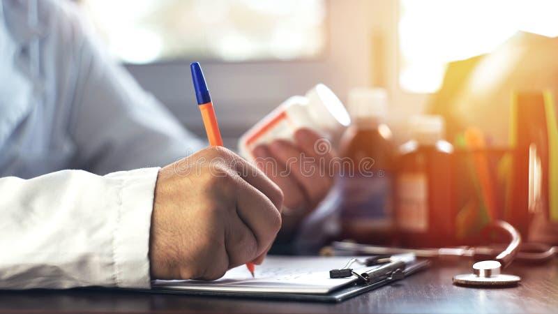 De handen die van de artsenmens rx voorschrift schrijven stock afbeeldingen
