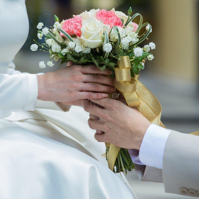 De handen die van Aziatische minnaars uitstekende bloem houden stock afbeeldingen