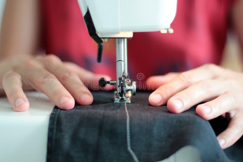 De handen die van de close-upnaaister aan naaimachine thuis werken Het naaien Proces vrouwenhanden achter het naaien close-up royalty-vrije stock fotografie