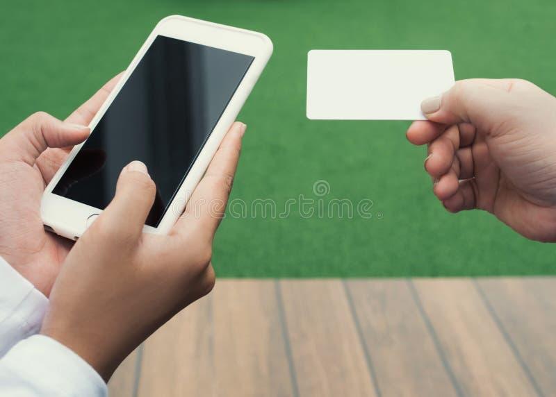 De handen die van de close-upvrouw een creditcard houden en celtelefoon, online openlucht winkelen met behulp van, stock afbeelding