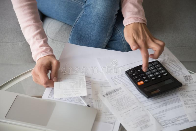 De handen die van de close-upvrouw het geld van calculatorkosten gebruiken beheren familiebegroting stock fotografie